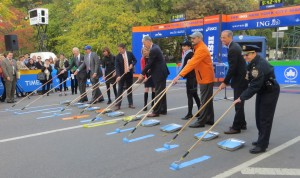 The ceremonial painting of the blue and yellow lines at the finish of the 2013 ING New York City Marathon. New York Road Runners president and CEO Mary Wittenberg is fifth from the left; to her immediate left is Tom Grilk, executive director of the Boston Athletic Association (photo by Chris Lotsbom for Race Results Weekly)