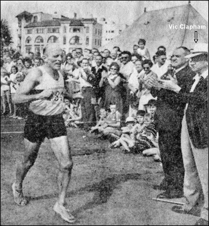 George Claassen crosses the finish line of the Comrades Marathon in 1961, watched by Comrades founder Vic Clapham. (Photo courtesy of the Comrades Marathon Association)