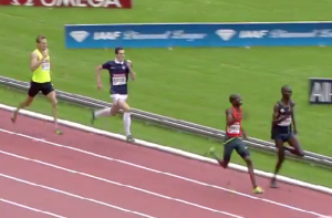 Kiprop and Amos Battle while a guy in a soccer uniform chases them.