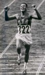 "Billy Mills winning the 10,000m in the 1964 Olympics: 1stLt William ""Billy"" Mills, USMCR, wove through a field of lapped runners and passed the race favorite, Ron Clarke of Australia, to win the 10,000 meters race at the 1964 Olympic Games. His victory is described as one of the greatest upsets in Olympic history and he is still the only American to ever win a gold medal in that event. Public Domain work of US Marine Corps see http://commons.wikimedia.org/wiki/File:BillyMills_Crossing_Finish_Line_1964Olympics.jpg"