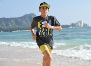Joshua Manning does strides before the 2014 Honolulu Marathon on Waikiki Beach with Diamond Head in the background (photo by Ronen Zilberman for the Honolulu Marathon)