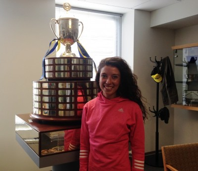 Emma Bates at the offices of the Boston Athletic Association with the Boston Marathon trophy (Photo by Chris Lotsbom for Race Results Weekly)