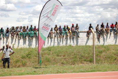 Spectators watch the Eldoret meeting from atop a wall outside the track