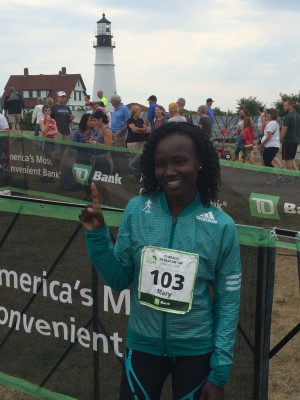 Keitany posing in front of the Portland Head Light near the finish line