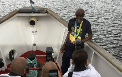 Mo Farah shows off one of his 2016 Olympic gold medals to photographers in advance of the 2016 Great North Run (photo by David Monti for Race Results Weekly)
