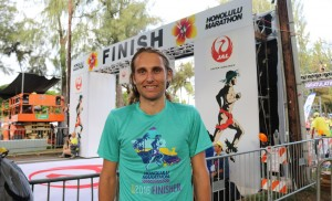 Hamish Carson proudly display's his 2016 Honolulu Marathon finisher's T-shirt (photo by Chris Lotsbom for Race Results Weekly)
