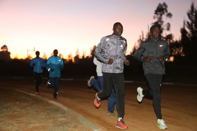 Eliud Kipchoge (r) warming up before sunset on the Moi University track
