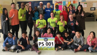 Liz Costello (third from right, back row) visiting Public School 1 in New York City in advance of the 2018 United Airlines NYC Half.  Also in photo, NYRR president of events and race director Peter Ciaccia (back row, center, in blue shirt) and NYRR senior vice president for Youth & Community Services Rachel Pratt (back row, second from right).  Photo courtesy of New York Road Runners